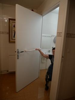 Photo montrant la porte d'accès aux sanitaires accessibles, équipée d'une barre de préhension jugée très utile