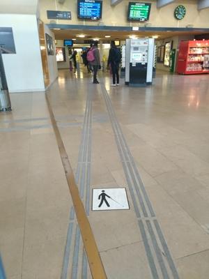 Cette photo prise depuis la porte de la gare montre les bandes rugueuses conduisant sur les quais, avec une intersection vers les guichets